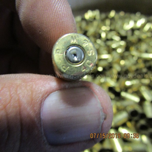 BRASS AMMUNITION SHELLS IN A BARREL ON A PALLET